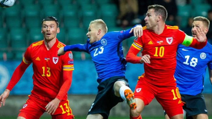 Estonia's Taijo Teniste fights for the ball with Wales' Kieffer Moore
