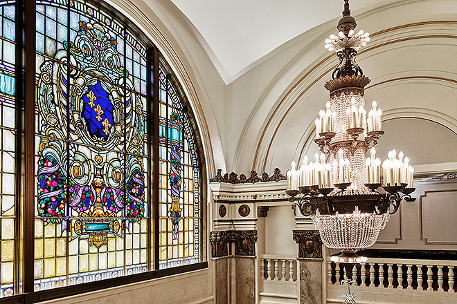 Restored stained glass window with a fleur-de-lis motif and a rolled celluloid strip.