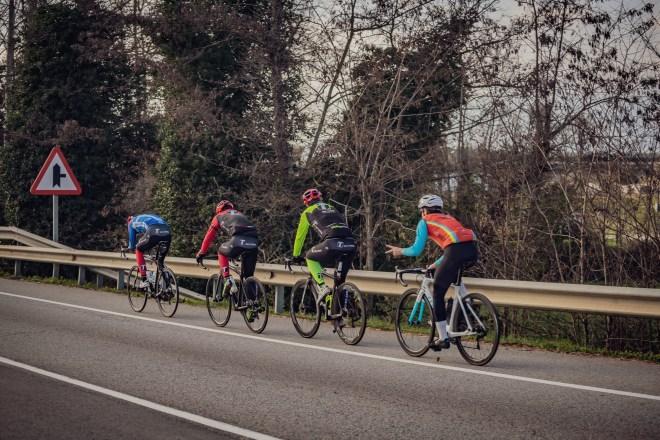 Varios ciclistas circulan en hilera por el arc