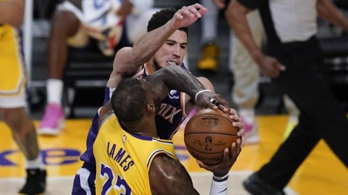 Devin Booker se interpone en el camino de LeBron James.