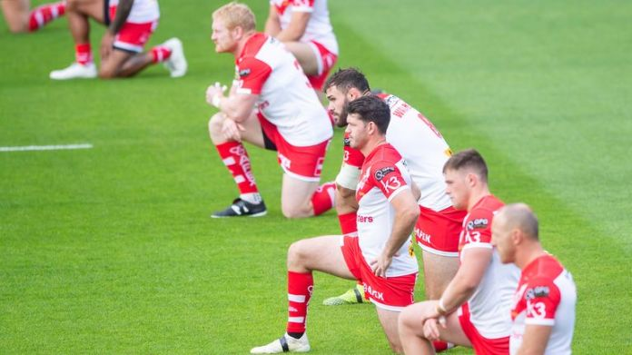 St Helens players take a knee ahead of their game against Catalans