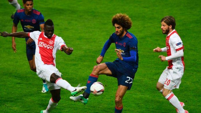 Ajax pair Davinson Sanchez (L) and Lasse Schone (R) vie for the ball with Marouane Fellaini (C)