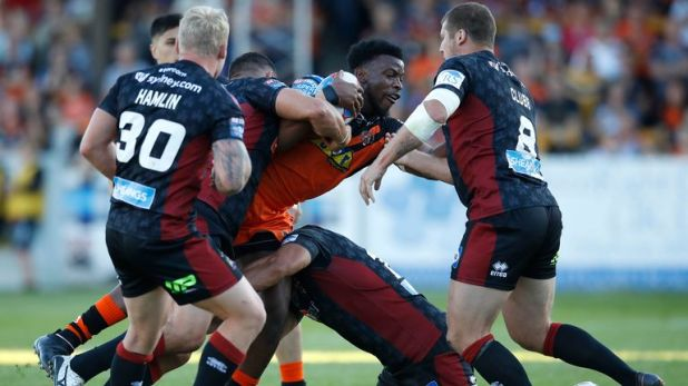 Castleford Tigers' Gadwin Springer is tackled by Wigan Warriors' Taulima Tautai and Tony Clubb