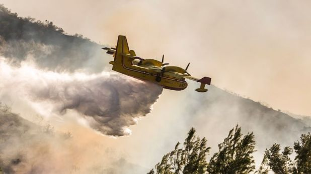 An airplane drops water on wildfires close to the 101 Freeway in Thousands Oaks, California