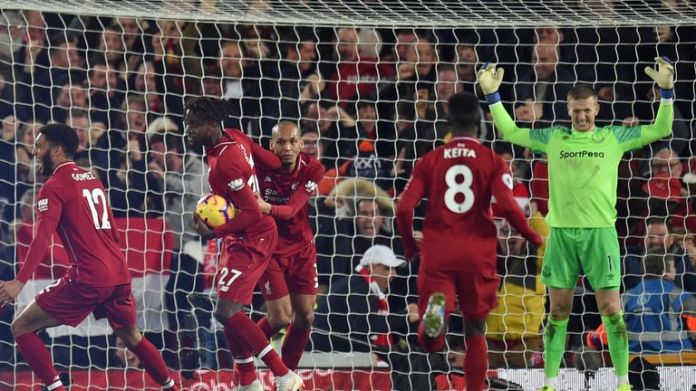 Divock Origi celebrates his 96th minute winner while Pickford grapples with his mistake
