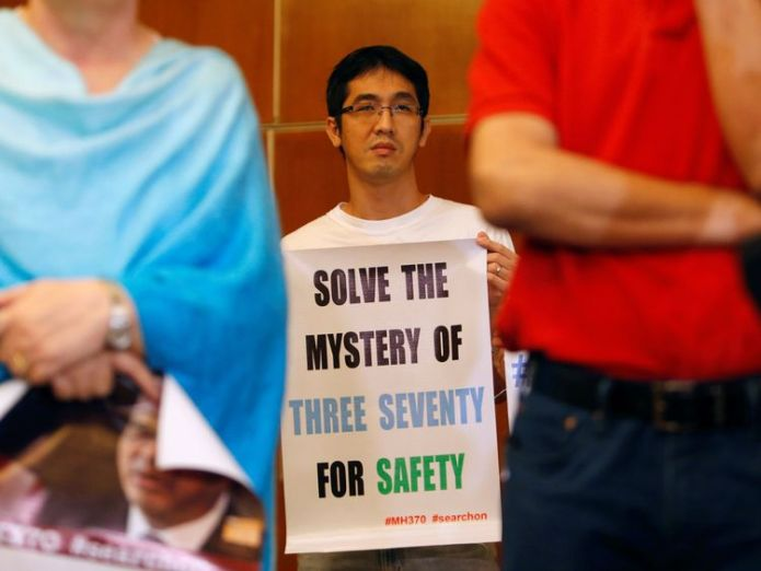 A family member of a passenger on the missing plane holds a placard pleading for continued searching Latest search for missing MH370 ends amid hope plane will be found Latest search for missing MH370 ends amid hope plane will be found 2496c19f4aa1d043fa483eaab1d6a23770d94cc64de59bbd61df1ae6d01bb17b 3748673