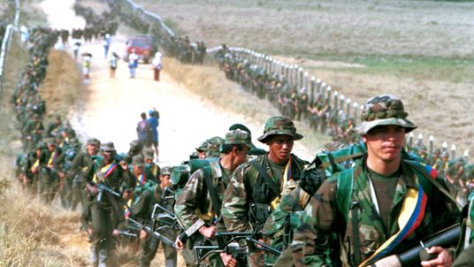 FARC rebels patrol a road in 1999