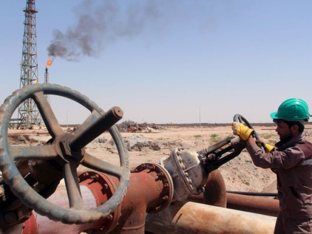 A worker checks the valve on a pipe at the Al-Sheiba oil refinery in the southern Iraqi city of Basra