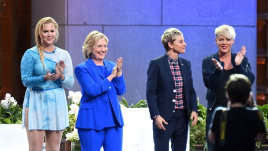 Hillary Clinton stands on stage with a number of female celebrities.