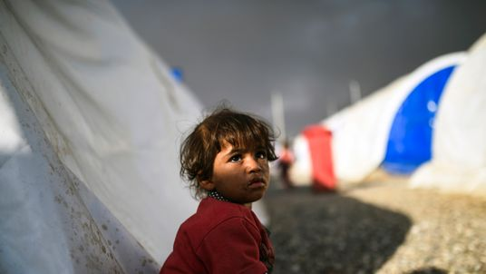 A displaced Iraqi girl looks on upon arriving to a refugee camp on October 22, 2016 in the town of Qayyarah, south of Mosul, as an operation to recapture the city of Mosul from the Islamic State group takes place