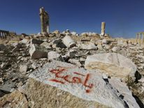 "IS graffiti reads ""we remain"" after Syrian troops recapture the ancient site of Palmyra"