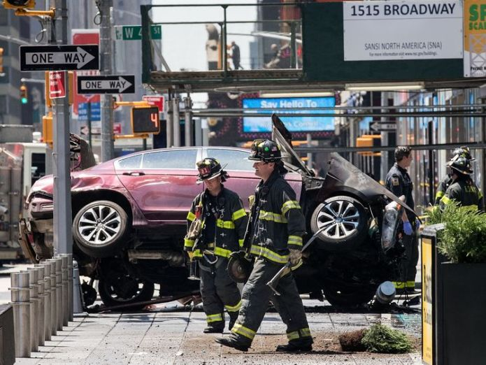 Firefighters walk past a wrecked car in the intersection of 45th and Broadway in Times Square, May 18, 2017 in New York City.