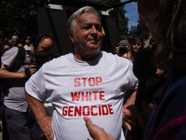 """A free speech rally participant wearing a """"stop white genocide"""" t-shirt speaks with a reporter outside..."""