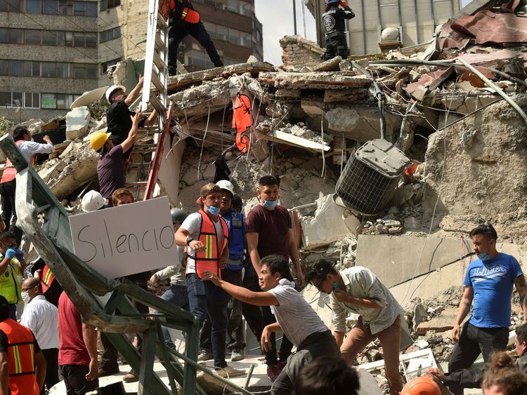 Rescuers display a placard reading 'Silence' as they hurry to free possible victims out of the rubble of a collapsed building after a quake rattled Mexico City on September 19, 2017
