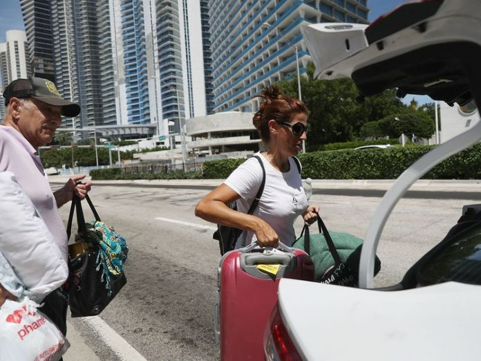 MIAMI BEACH, FL - SEPTEMBER 08: Dario Perdomo and Alejandra Valde (L-R) take a Lyft ride to a shelter as they evacuate their condos before the arrival of Hurricane Irma on September 8, 2017 in Miami Beach, Florida. Florida appears to be in the path of the Hurricane which may come ashore at category 4. (Photo by Joe Raedle/Getty Images)