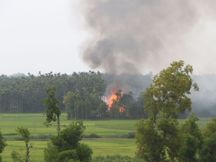 Thick black smoke rises from what is believed to be a burning village in western Myanmar