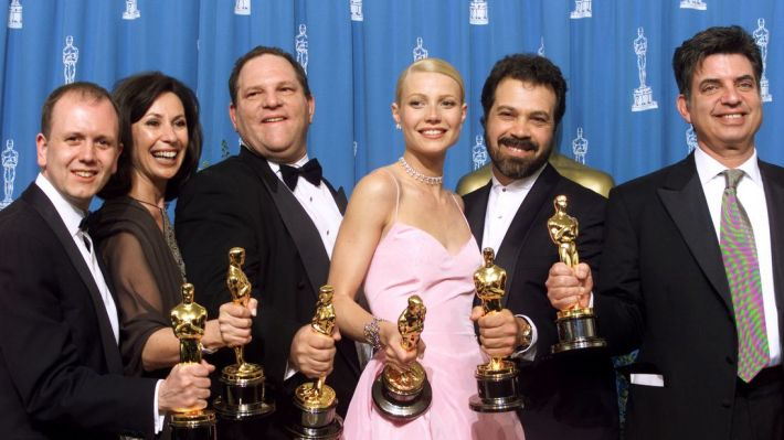 Gwyneth Paltrow celebrates the Oscar she won for Shakespeare in Love with the producers of the film, including Harvey Weinstein (3rd left)