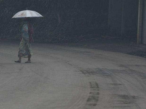 A woman uses an umbrella as she walks through ash from Mount Agung volcano during an eruptiuon in Bebandem Village, Karangasem, Bali