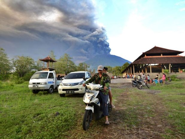 Balinese people look at Mount Agung during an eruption seen from Kubu sub-district