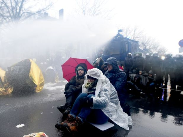 Protesters attempt to withstand the water by using umbrellas