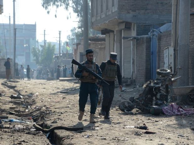 Afghan security force members inspect the site of blast near a TV station in Jalalabad