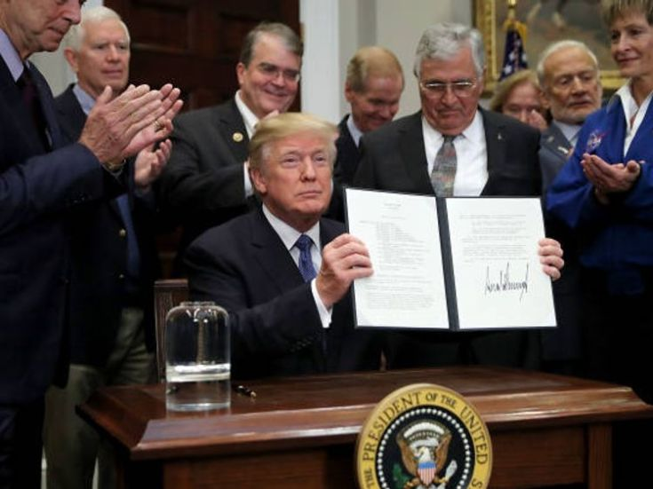President Donald Trump holds up 'Space Policy Directive 1' after signing it during a ceremony with NASA astronauts Peggy Whitson, Buzz Aldrin and Jack Schmitt