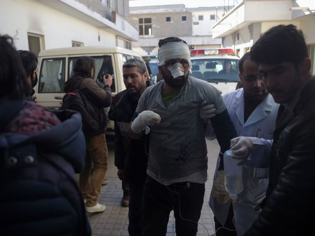 An injured Afghan man is led from an ambulance to a hospital following blasts at a Shiite cultural centre in Kabul on December 28, 2017. At least 40 people were killed and dozens more wounded in multiple blasts at a Shiite cultural centre in Kabul on December 28, officials said, in the latest deadly violence to hit the Afghan capital. / AFP PHOTO / SHAH MARAI (Photo credit should read SHAH MARAI/AFP/Getty Images)