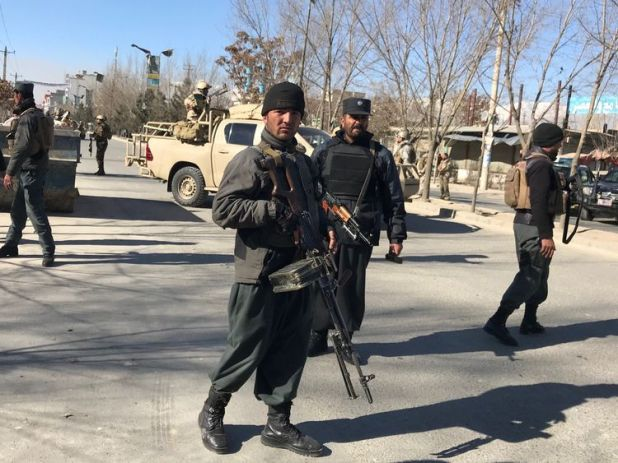 Afghan policemen stand guard at the site of a blast in Kabul, Afghanistan