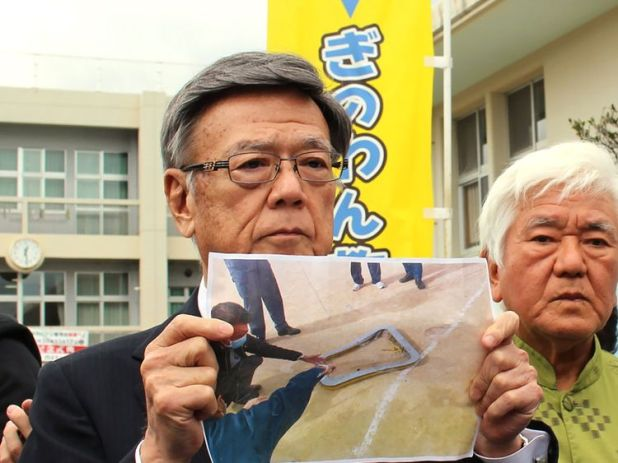 Okinawa's governor stands stood outside the school and showed a picture of the window