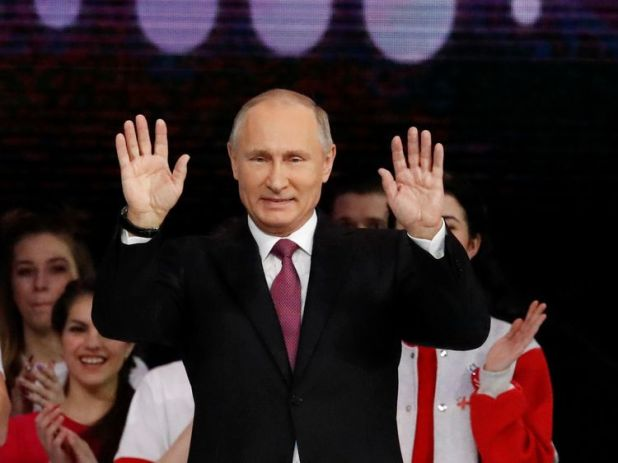 Russian President Vladimir Putin greets the audience at the congress of volunteers in Moscow