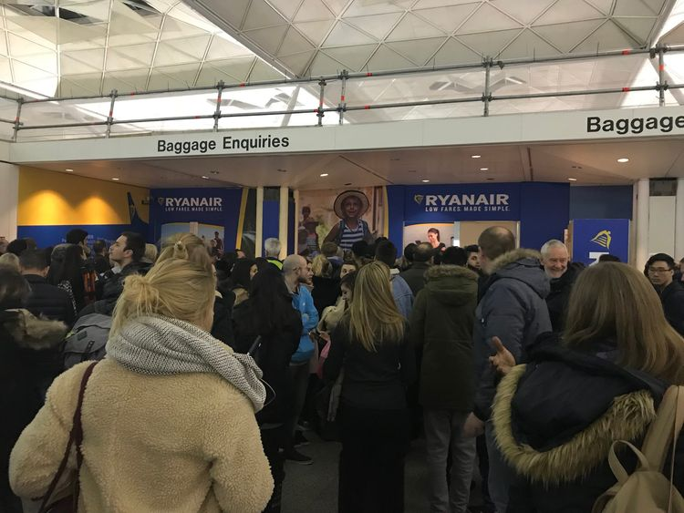 Passengers wait for information at Stansted Airport. Pic: Sophia Sleigh