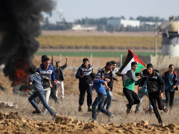Palestinian protesters run during clashes in the southern Gaza Strip