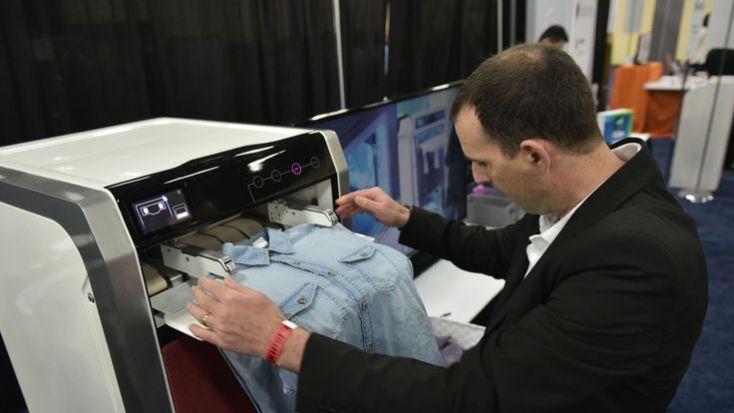 An exhibitor demonstrates the FoldiMate laundry folding machine