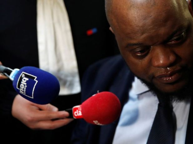Bley Bilal Mokono, who was injured during the Stade de France attack, cries as he talks to journalists before the start of the trial of Jawad Bendaoud