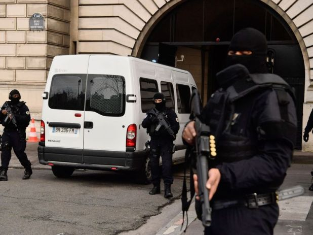 Armed French police stand guard as a van carrying Jawad Bendaoud, charged with harbouring jihadists during the November 2015 terror attacks, arrives at the courthouse of Paris on January 24, 2018. The first trial stemming from the November 2015 Paris terror attacks opens when Jawad Bendaoud appears in court, charged with harbouring two of the jihadists in the aftermath of the carnage. / AFP PHOTO / CHRISTOPHE SIMON (Photo credit should read CHRISTOPHE SIMON/AFP/Getty Images)