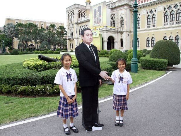 Children pose next to a cardboard cut-out of Thailand's Prime Minster Prayuth Chan-ocha