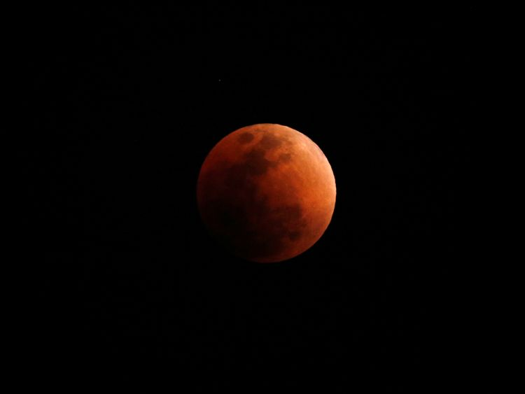 """A """"super blood blue moon"""" is seen during an eclipse, behind an office building in Hong Kong, China"""