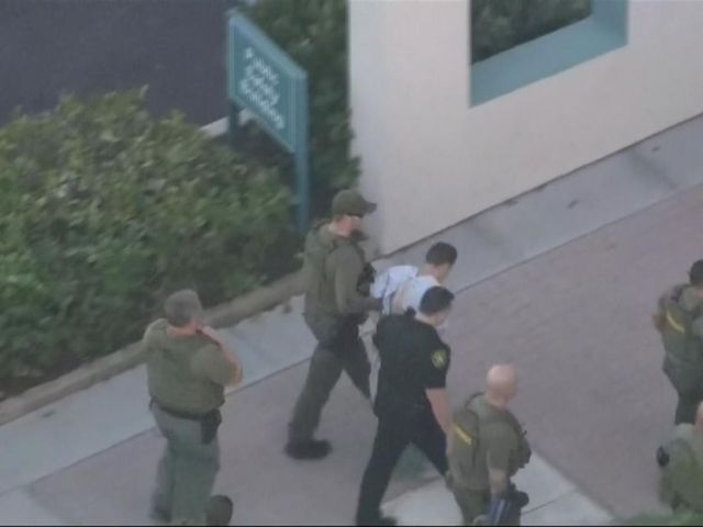 The suspect in the Florida school shooting is led into hospital