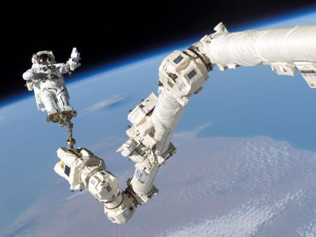 IN SPACE - AUGUST 3: In this NASA handout, mission specialist, Astronaut Stephen K. Robinson, is anchored to a foot restraint on the International Space Station's Canadarm2 robotic arm, during his space walk to repair the underside of the space shutttle Discovery August 3, 2005. Space shuttle Discovery is scheduled to return to Earth August 8. (Photo by NASA via Getty Images)