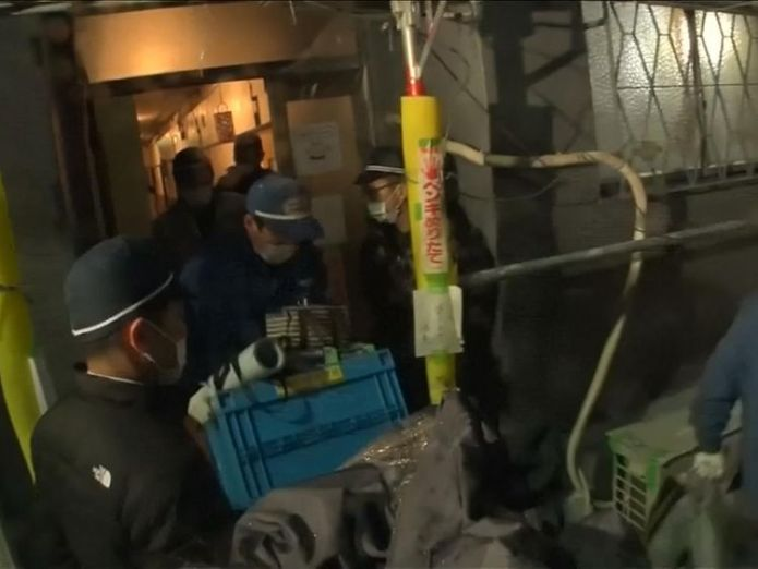 Police leaving the building carrying items from the apartment US man arrested in Japan after woman's severed head found in suitcase US man arrested in Japan after woman's severed head found in suitcase skynews japan yevgeniy bayraktar 4242181
