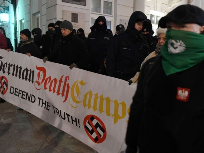 Far-right protesters hold a banner during a demonstration to support a controversial new Polish bill regarding the Holocaust and the definition of Nazi death camps on February 5, 2018 outside the presidential palace in Warsaw. The legislation, which still needs President Andrzej Dudas signature to take effect, is intended to stop people from erroneously describing Nazi German death camps as being Polish. / AFP PHOTO / JANEK SKARZYNSKI (Photo credit should read JANEK SKARZYNSKI/AFP/Getty Images)  Polish PM Mateusz Morawiecki defends 'Jewish Holocaust perpetrators' comments Polish PM Mateusz Morawiecki defends 'Jewish Holocaust perpetrators' comments skynews poland holocaust protest 4234607