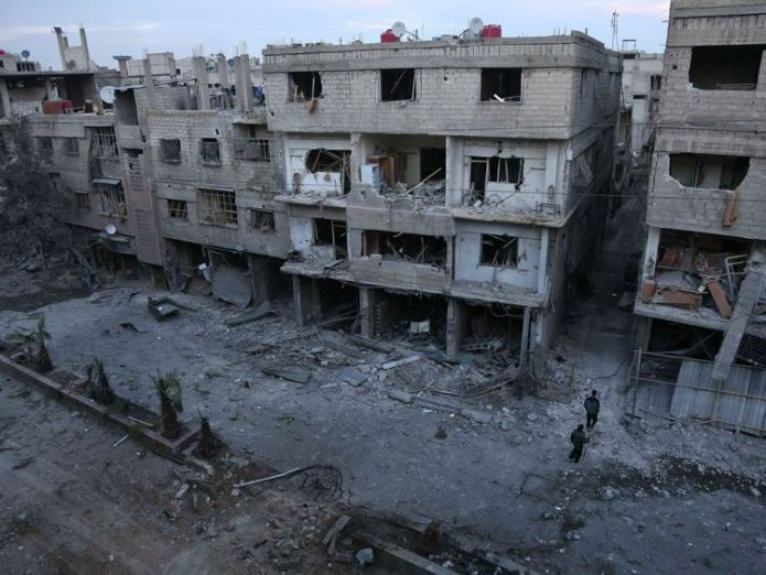 Syrian civilians look at the rubble following government bombing on the outskirts of the capital Damascus 'Deadliest day' in years as women and children killed near Damascus 'Deadliest day' in years as women and children killed near Damascus skynews syria damascus government bombing 4235802