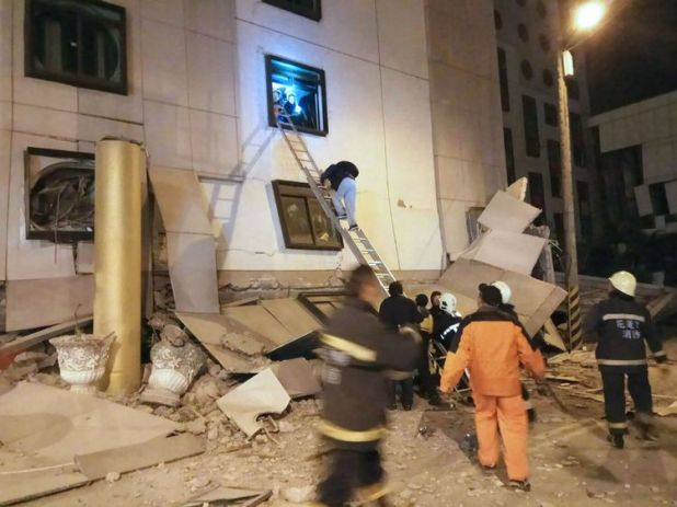 Rescue workers search through rubble outside the Marshal Hotel in Hualien, eastern Taiwan early February 7, 2018, after a strong earthquake struck the island. A hotel on the east coast of Taiwan has collapsed after a 6.4-magnitude earthquake, the government said. / AFP PHOTO / STR / Taiwan OUT (Photo credit should read STR/AFP/Getty Images)