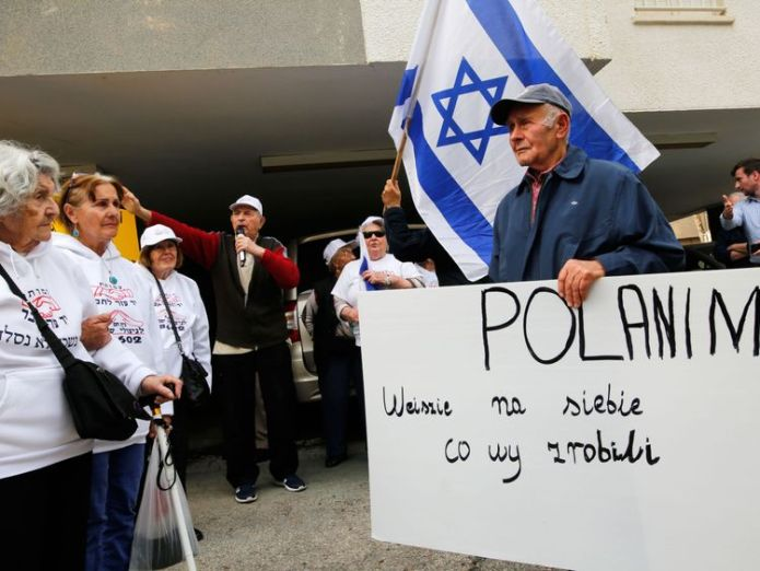 Holocaust survivors hold banners and wave an Israeli flag during a protest in front of Polish embassy in Tel Aviv on February 8, 2018, against a controversial bill passed by the eastern European country's senate. The legislation sets fines or a maximum three-year jail term for anyone describing Nazi German death camps in Poland, like Auschwitz-Birkenau, as Polish. / AFP PHOTO / GIL COHEN-MAGEN (Photo credit should read GIL COHEN-MAGEN/AFP/Getty Images)  Polish PM Mateusz Morawiecki defends 'Jewish Holocaust perpetrators' comments Polish PM Mateusz Morawiecki defends 'Jewish Holocaust perpetrators' comments skynews tel aviv israel poland 4234604