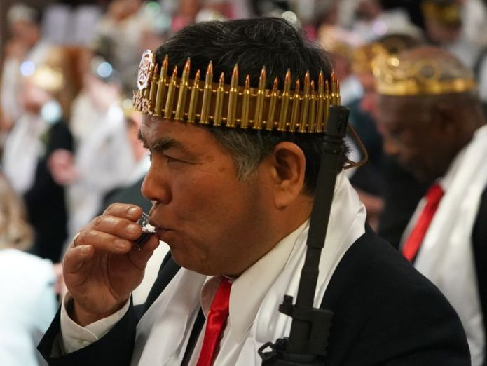 A man wearing a crown of rifle shells takes communion Worshippers armed with AR-15s celebrate their marriages and weapons at a church in Pennsylvania Worshippers armed with AR-15s celebrate their marriages and weapons at a church in Pennsylvania guns church sky news 4243545