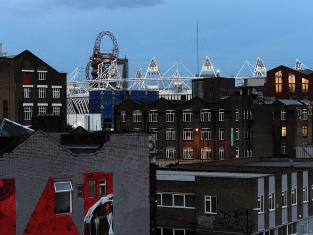 The Olympic stadium is seen beyond the rooftops of Hackney Wick