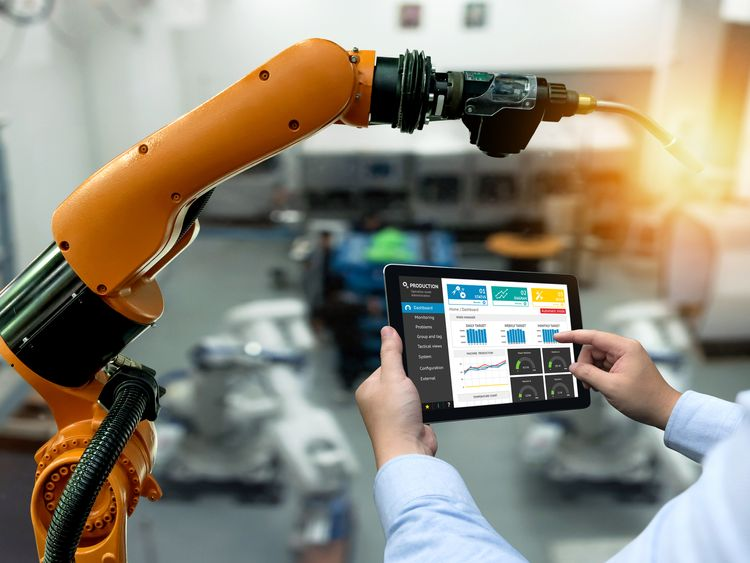 Engineer hand using tablet and heavy automation robot arm machine in factory