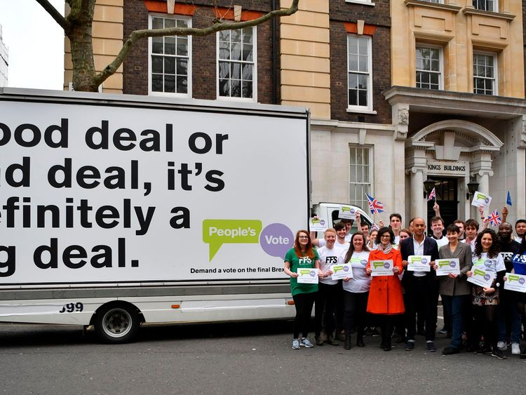 Labour MP Chuka Umunna (C), Lib Dem MP Layla Moran (CL) and Green MP Caroline Lucas (CR) pose with activists in front of an advertising board to launch the People's Vote advertising campaign