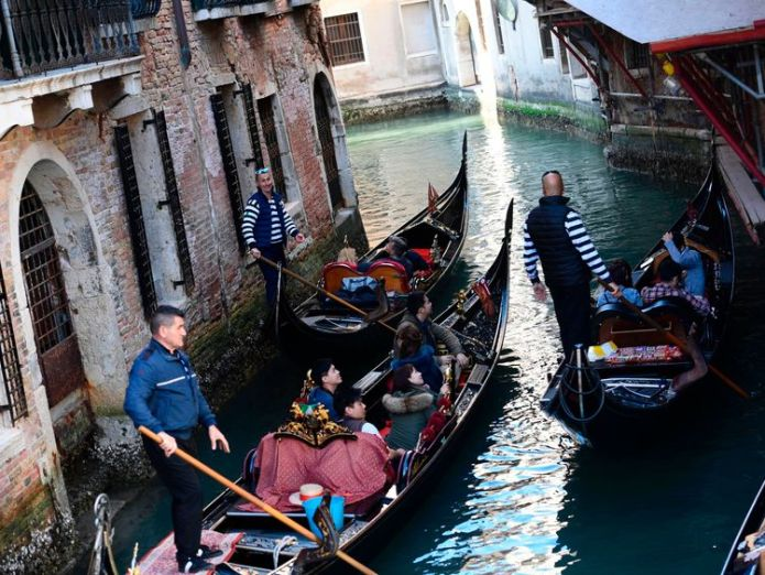 Tourists sit in gondolas on the Grand Canal in Venice  Tourists face €500 fine for sitting down in Venice skynews venice gondola 4295349