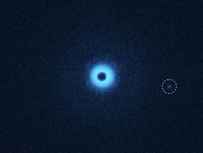 An infrared image of the binary star and the newly discovered companion, but now viewed with special polarization filters that make dust discs and exoplanets visible. The companion seems to have his own dust disc. Credit: C. Ginski & SPHERE